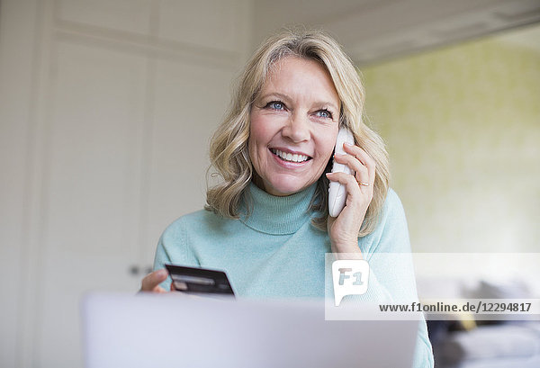 Smiling mature woman with credit card talking on telephone at laptop
