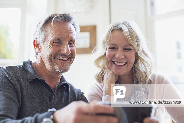 Smiling mature couple using smart phone