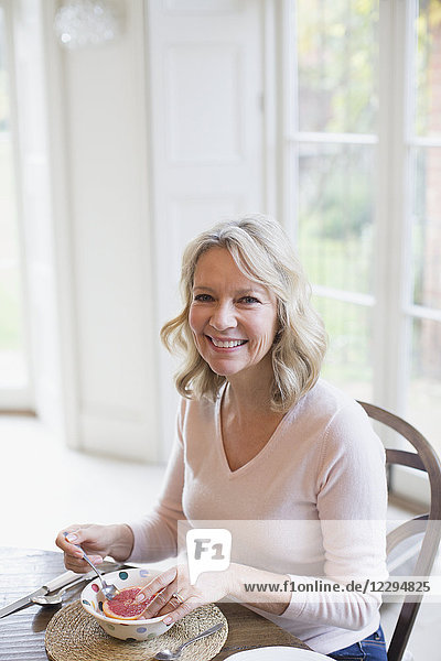 Portrait smiling mature woman eating grapefruit