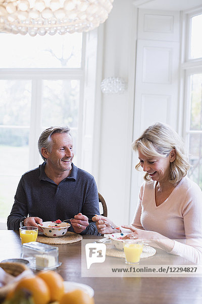 Smiling mature couple eating breakfast at dining table