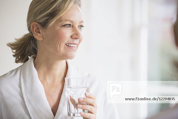 Smiling mature woman in bathrobe drinking water