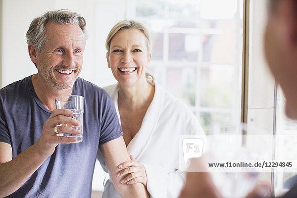 Smiling mature couple at bathroom mirror