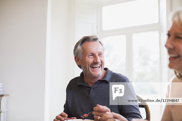 Laughing mature couple eating