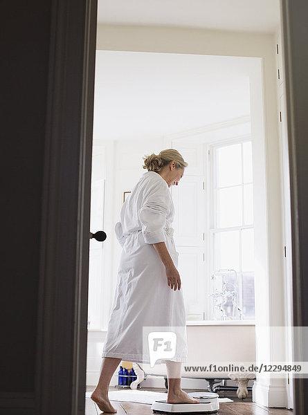 Mature woman in bathrobe stepping on bathroom scale