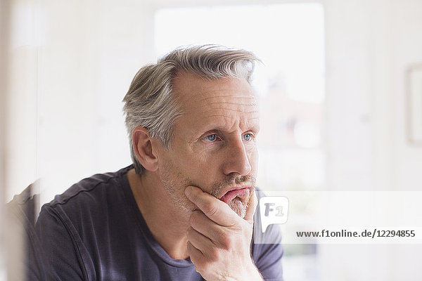 Mature man touching face in bathroom mirror