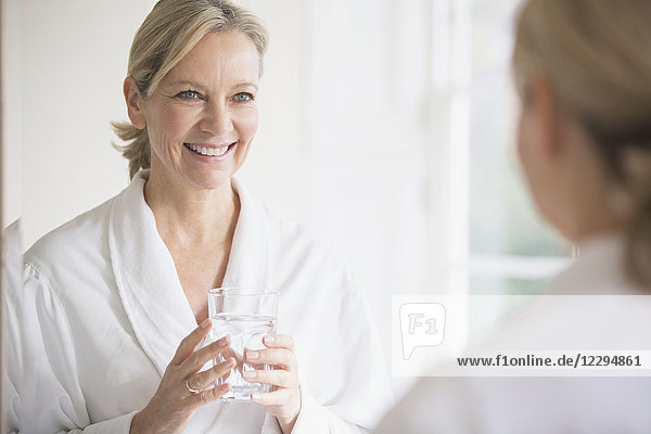 Smiling  confident mature woman in bathrobe drinking water at bathroom mirror
