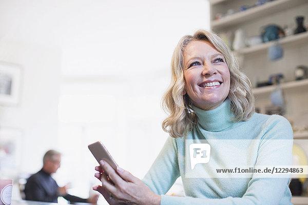 Smiling  confident mature woman using smart phone