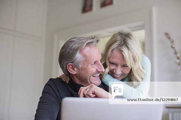 Laughing  carefree mature couple using laptop
