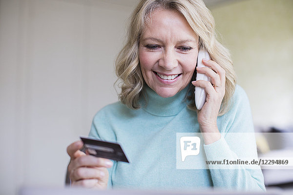 Smiling mature woman with credit card talking on telephone