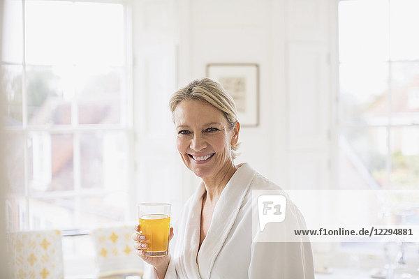 Portrait smiling  confident mature woman in bathrobe drinking juice