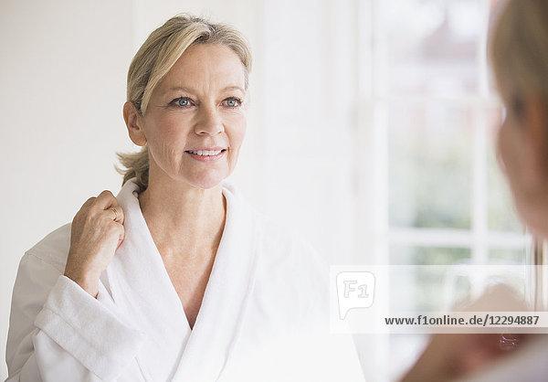 Smiling mature woman in bathrobe at bathroom mirror