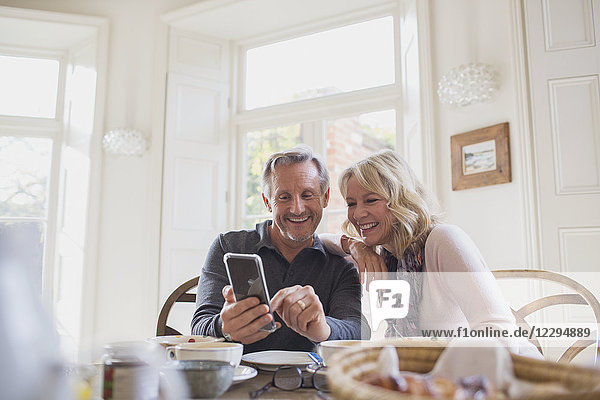 Smiling mature couple using smart phone at dining table