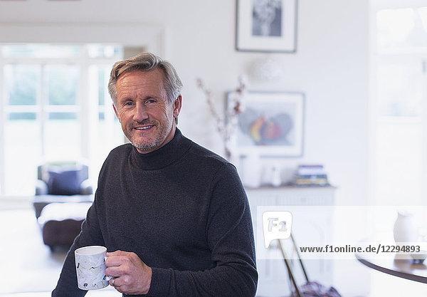 Portrait confident mature man drinking coffee in kitchen