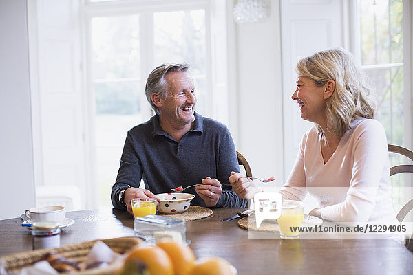 Smiling mature couple eating breakfast and talking at dining table