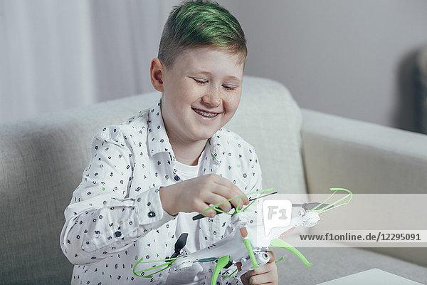 Lächelnder Junge  der zu Hause auf dem Sofa sitzt und die Drohne anpasst.