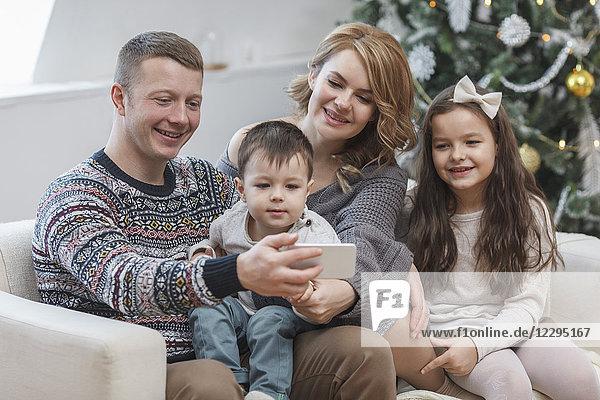 Glücklicher Mann  der sein Handy mit seiner Familie zu Hause auf dem Sofa teilt.