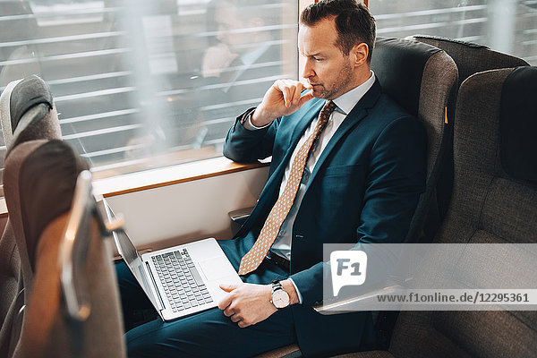 High angle view of businessman using laptop while traveling in train