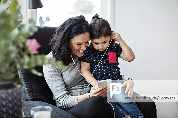 Mother and daughter wearing headphones while listening music through mobile phone in living room
