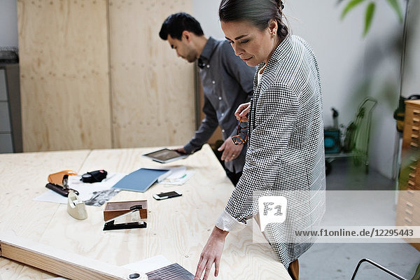 Businesswoman reading file while businessman using digital tablet at table in meeting