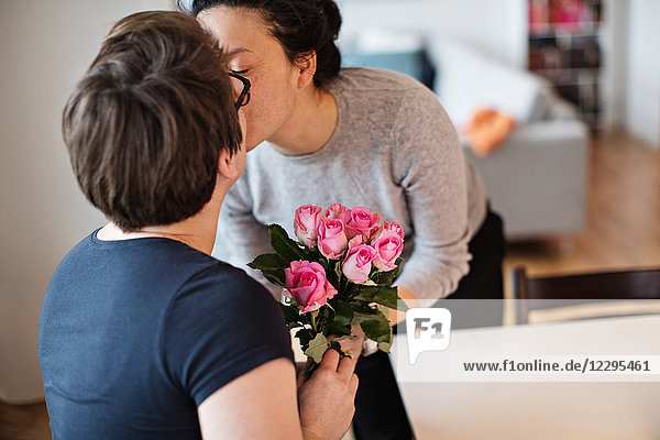 Close-up of lesbian couple kissing while holding pink roses at home
