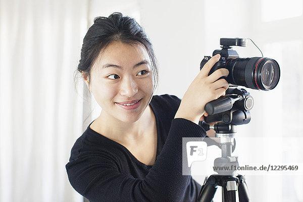 Lächelnde junge Frau beim Fotografieren mit der Kamera