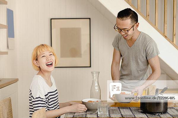 Glückliches junges Paar genießt das Essen auf dem Esstisch zu Hause