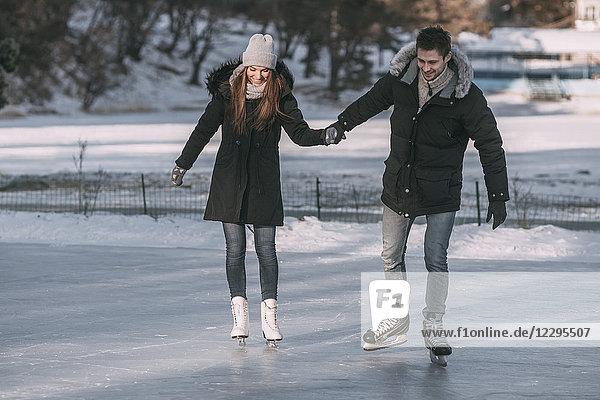 Volle Länge des Mannes  der mit der Frau Händchen hält  während er auf der Eisbahn Schlittschuh läuft.