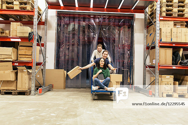 Male and female coworkers enjoying while working at warehouse