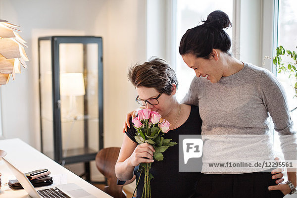 Smiling woman looking at girlfriend smelling pink roses at home