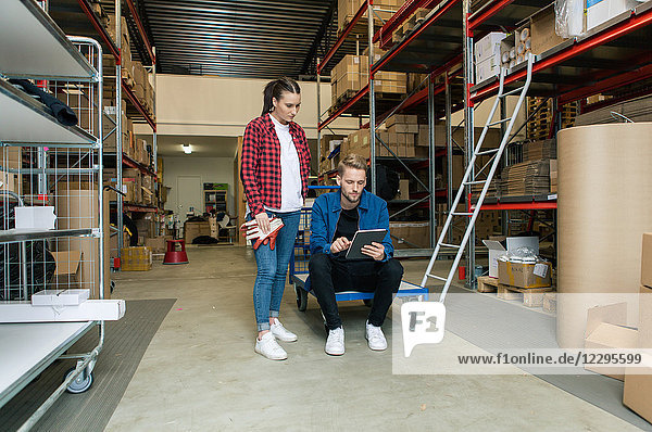 Female coworker looking at manager using digital tablet in warehouse