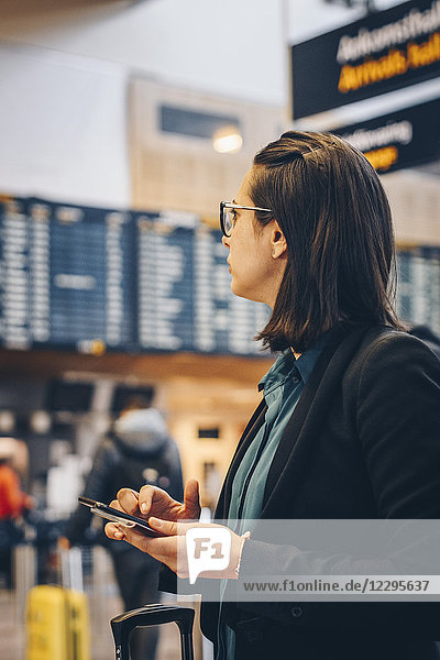 Mid adult businesswoman using mobile phone while standing in airport