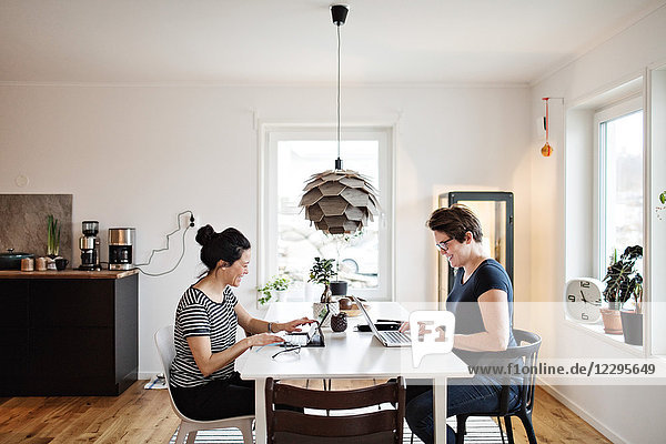 Side view of smiling women using laptop while sitting at table in living room