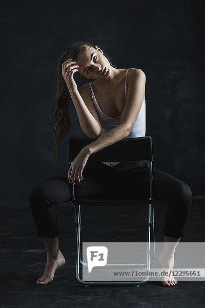 Ganzflächiges Porträt eines jungen Models  das auf einem Stuhl auf schwarzem Hintergrund sitzt.