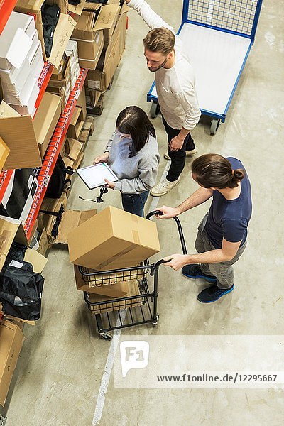 High angle view of woman using digital tablet while male coworkers analyzing in boxes