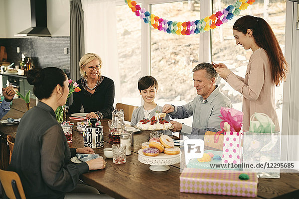 Multi-generation family enjoying birthday cake at table during party