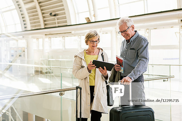 Senior woman holding digital tablet by man standing with luggage at subway station
