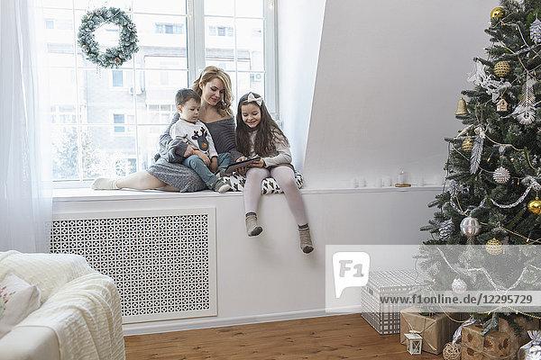 Frau sitzend mit Kindern auf der Fensterbank zu Hause zu Weihnachten