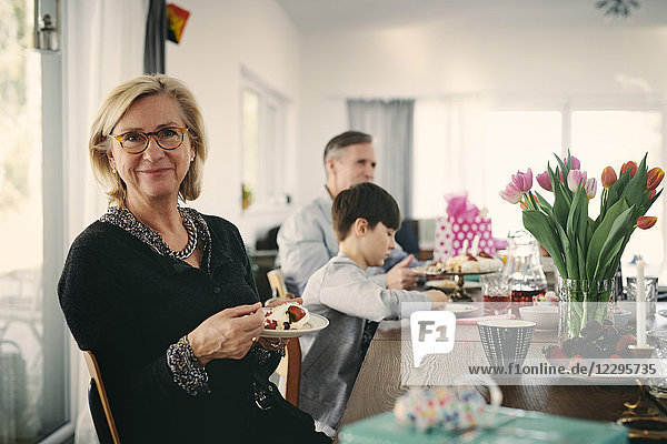 Portrait of smiling grandmother having cake while sitting with family at table during party