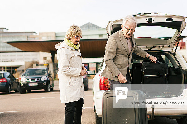 Senior man unloading luggage from car trunk by woman standing in parking lot