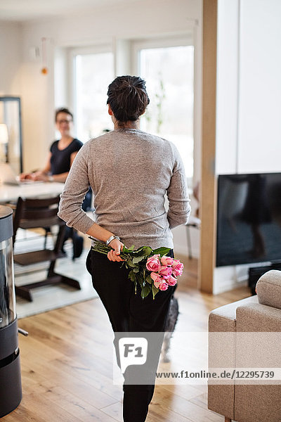 Rear view of woman hiding bouquet while walking towards girlfriend at home
