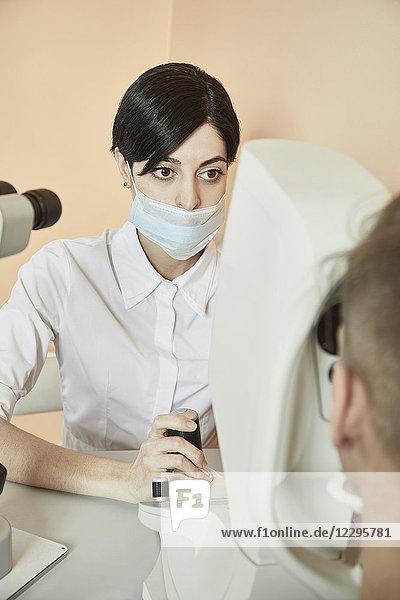 Augenoptiker bei der Untersuchung des Patientenauges im Krankenhaus