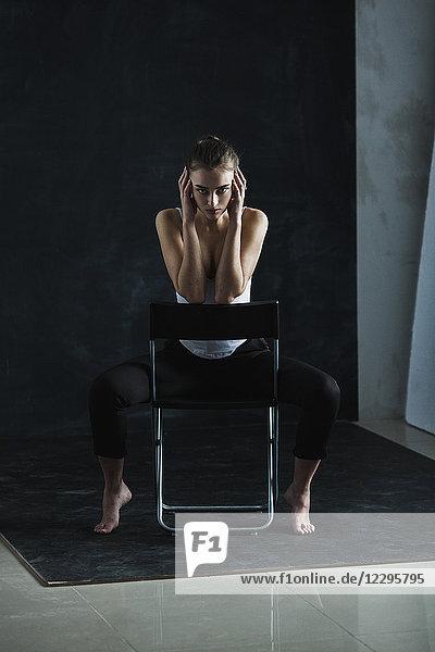 Ganzflächiges Porträt eines jungen Models auf einem Stuhl vor schwarzem Hintergrund.