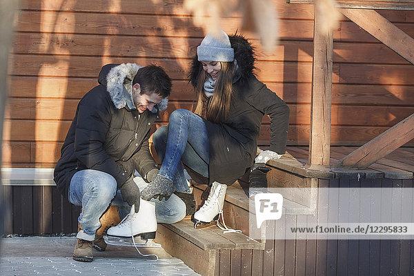 Mann hockt und unterstützt glückliche Frau beim Tragen von Schlittschuhen auf Stufen