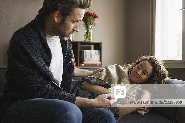 Mann gibt Pillen an kranke Frau  die auf dem Sofa im Wohnzimmer liegt.
