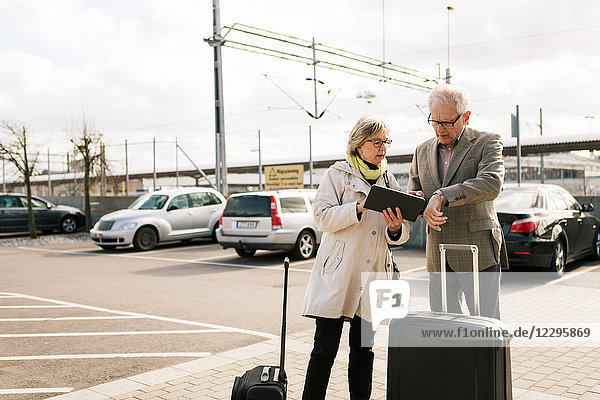 Senior couple using digital tablet while standing with luggage at parking lot against sky
