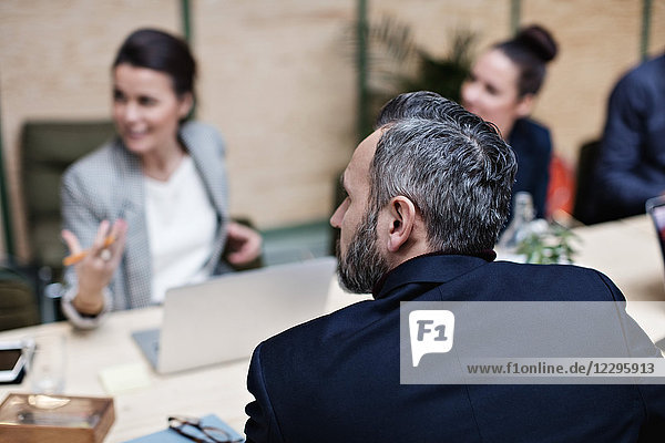 Businessman listening to colleagues during meeting at office