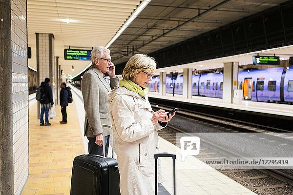 Senior couple using smart phones while standing with luggage at illuminated subway station