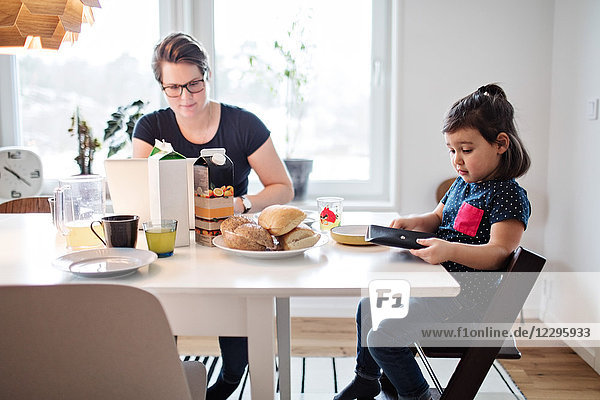 Mother using laptop while sitting with daughter during breakfast at table