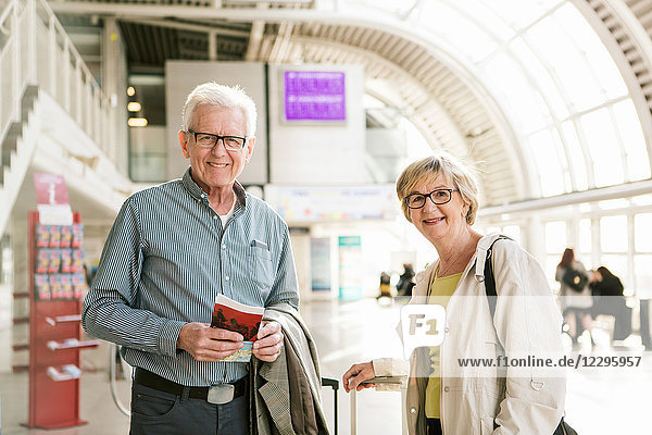Portrait of smiling senior couple standing with book and luggage at subway station