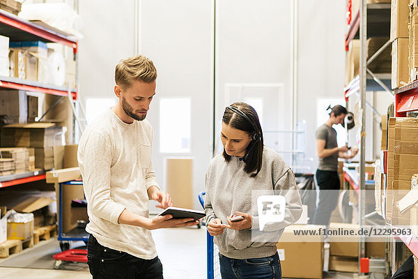 Coworkers looking at digital tablet while planning in distribution warehouse